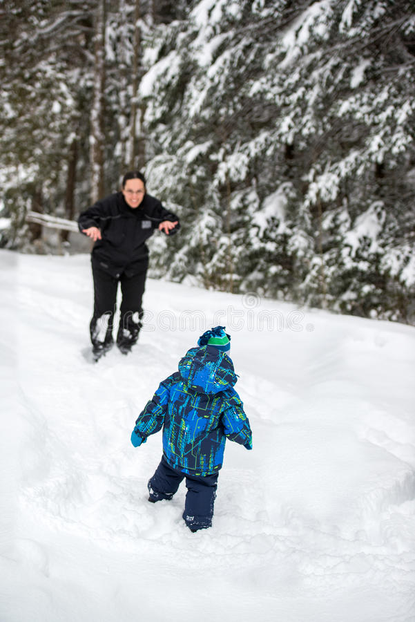 Mother Playing with Son Outside in the Snow royalty free stock photos
