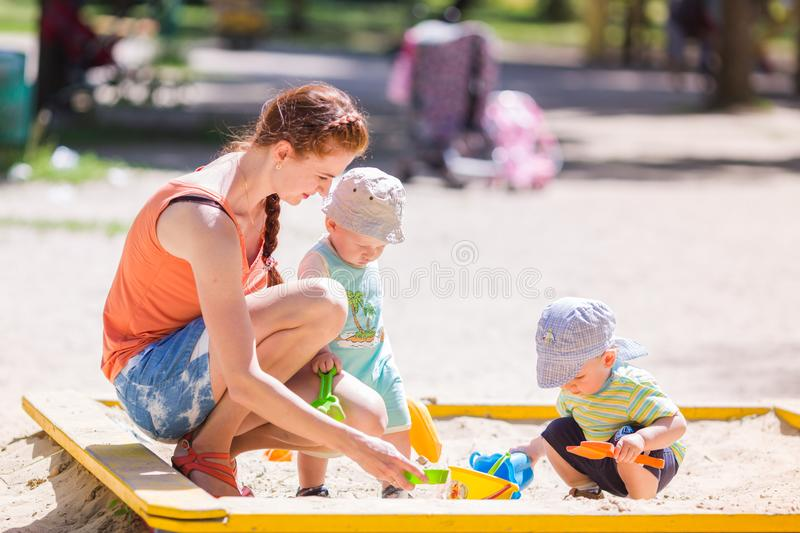 Mother playing with two baby boys stock photos
