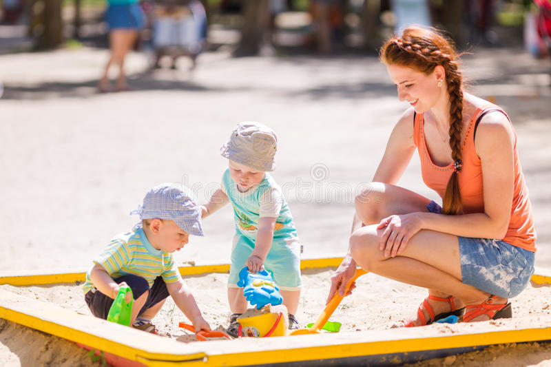 Mother playing with two baby boys royalty free stock photo