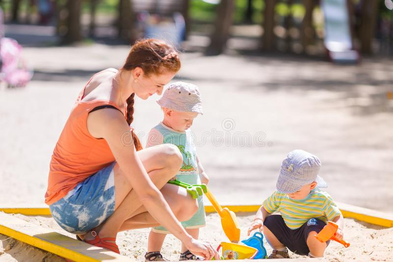 Mother playing with two baby boys stock photography