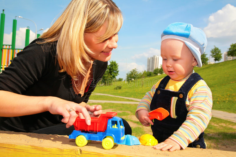 Mother plays with child with toy car stock photography