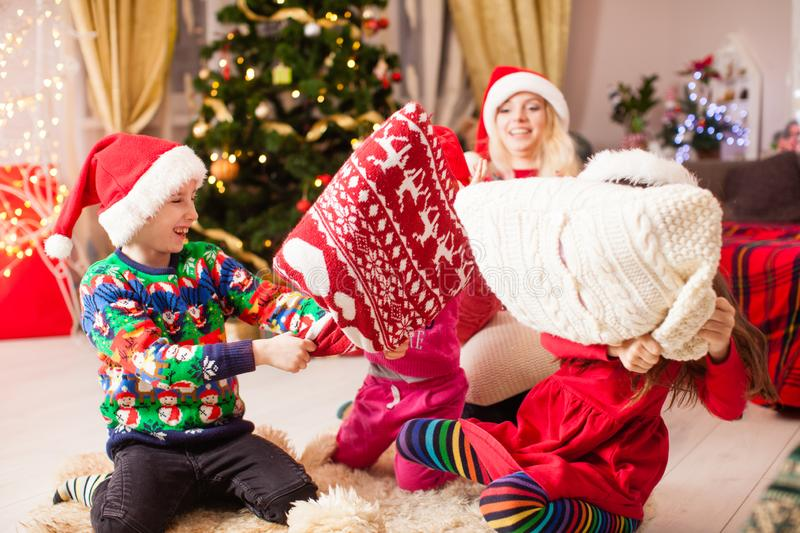 Mother plays with children at Chrismtas evening party on the floor. Brother and sister at the Chrismtas evening party, children hold hands battle pillow, floor royalty free stock photos
