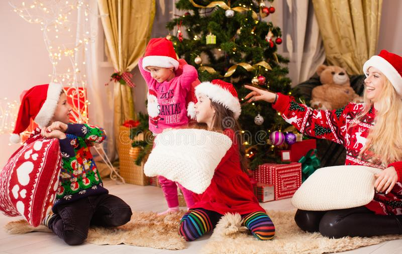 Mother plays with children at Chrismtas evening party on the floor. Mother plays with children at Chrismtas evening party, kids hold hands battle pillow, floor stock image