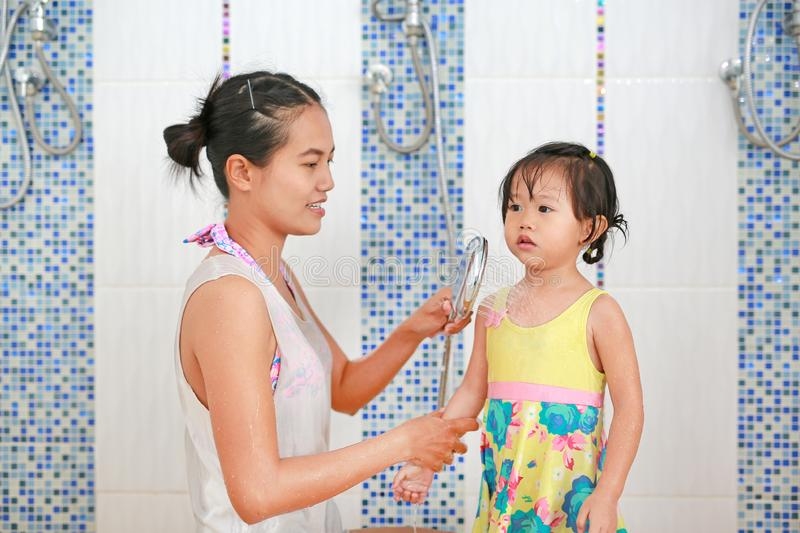 Mother pours water from shower for child to warm up body before swim stock images