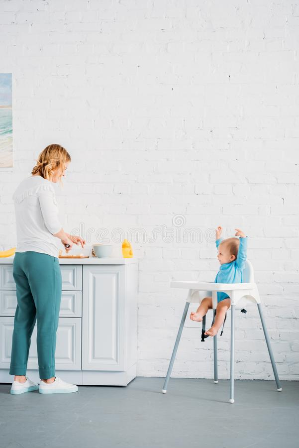 Mother preparing dinner for her excited little child. While he sitting in feeding chair at kitchen royalty free stock images