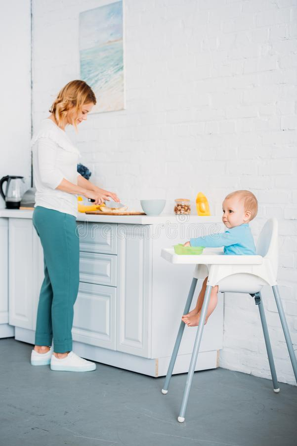 Mother preparing dinner for her little child. While he sitting in feeding chair at kitchen stock image