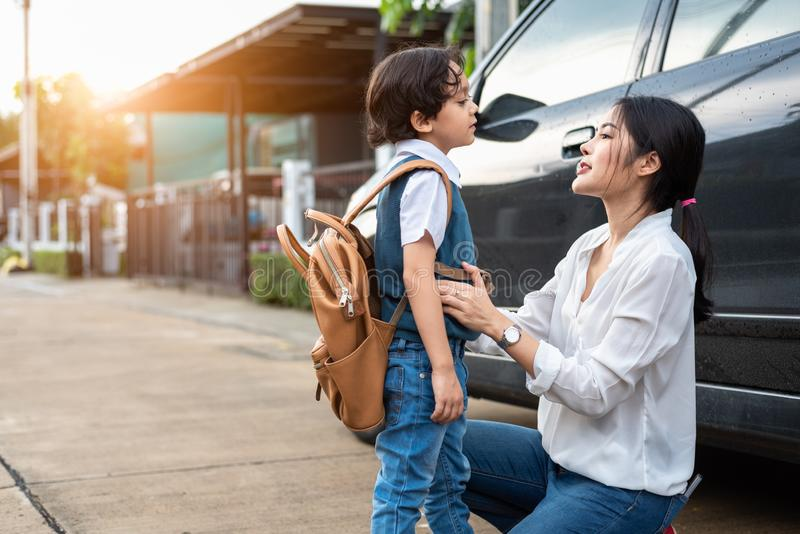 Mother preparing to send her children back to school at car in morning. Mom say Good bye before school start. Education and Back royalty free stock photography