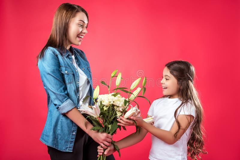 Mother presenting bouquet of flowers to daughter royalty free stock image