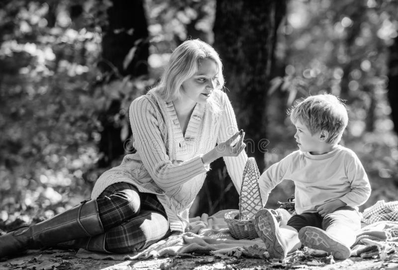 Mother pretty woman and little son sit on plaid relaxing forest picnic. Good day for spring picnic in nature. Explore stock photography