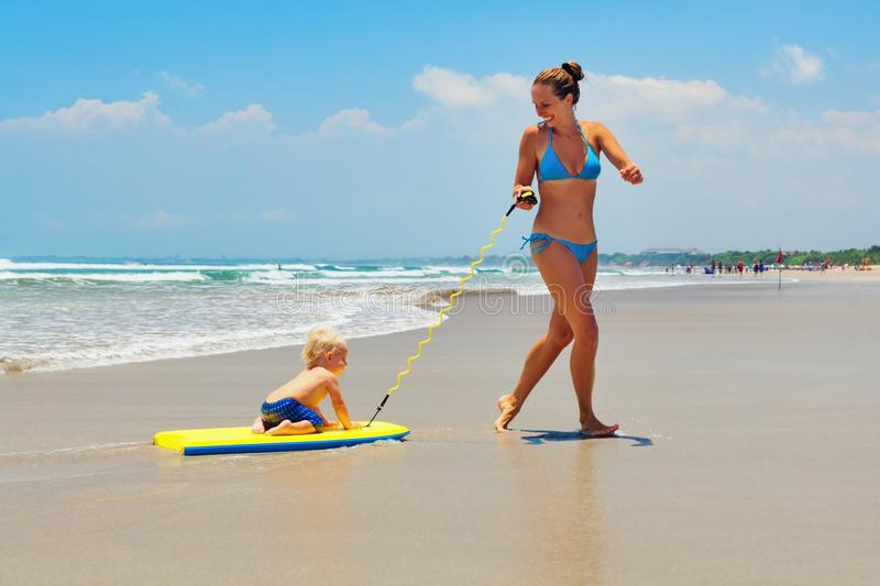 Mother pull baby son on surfing board by sea beach. Happy family having fun - mother run and pull baby son on surfing board by water pool along sea surf of beach stock photo