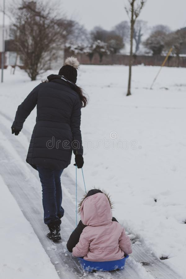 A mother pulls her kids on a blue snow sled royalty free stock photos