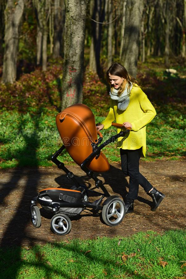 Mother push baby stroller in spring park. Young mother with pram on walk. Nothing feels as good as being a mom.  stock photos