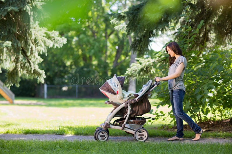 Mother Pushing Stroller In The Park stock photography