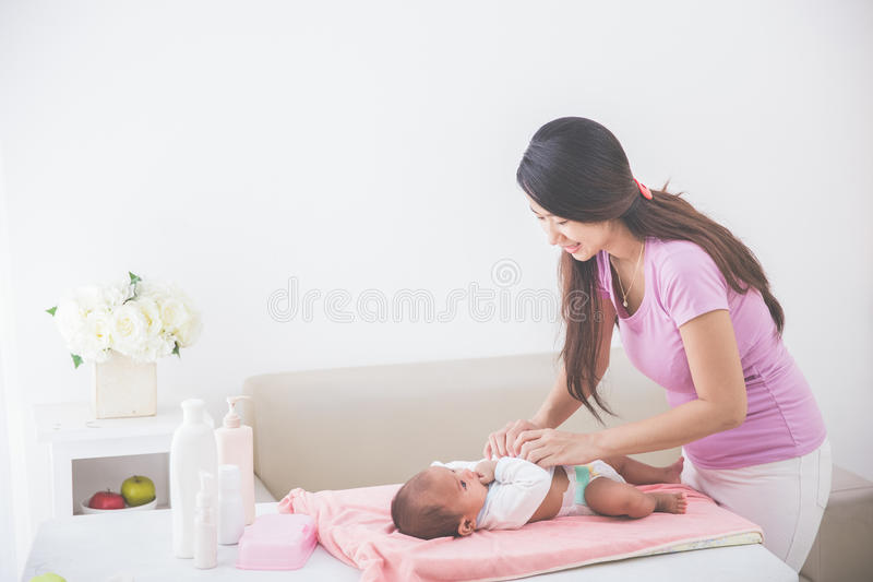 Mother put on some clothes to her baby royalty free stock photos
