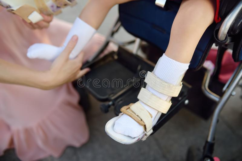 Mother puts on orthosis her daughter legs. Disabled girl sitting on a wheelchair. Child cerebral palsy. Inclusion stock images