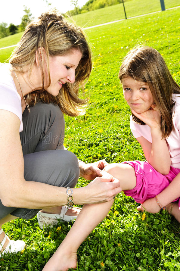 Mother putting bandage on child. Portrait of mother giving first aid to daughters cut knee royalty free stock images