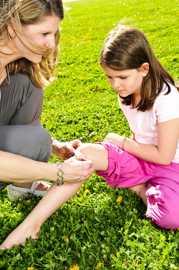 Mother putting bandage on child. Portrait of mother giving first aid to daughters cut knee royalty free stock photo