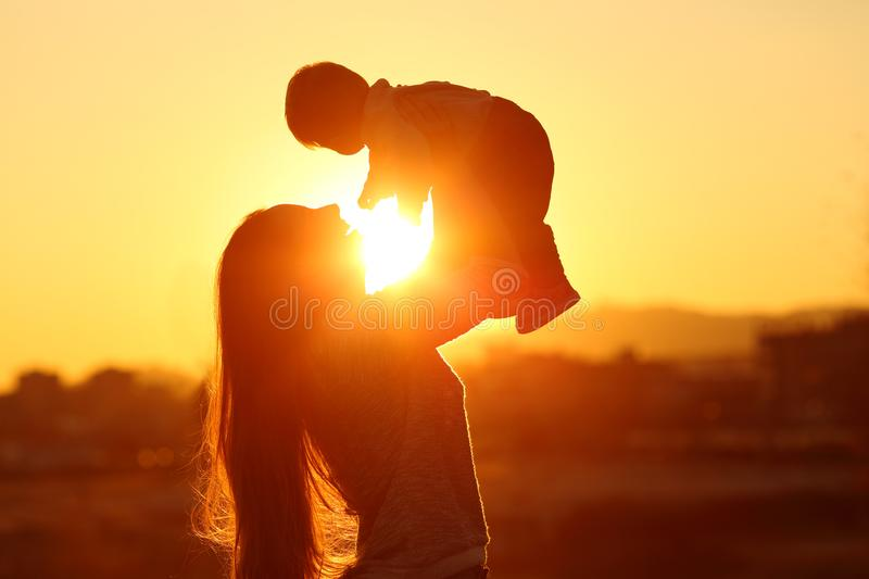 Mother raising her kid son at sunset with the sun in the middle stock image