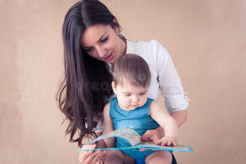 Mother reading a book to her baby girl stock photos