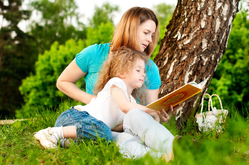 Mother reading book to her daughter stock images
