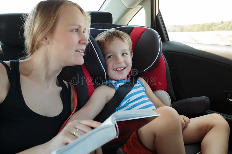Mother reading a book to son in the car royalty free stock image