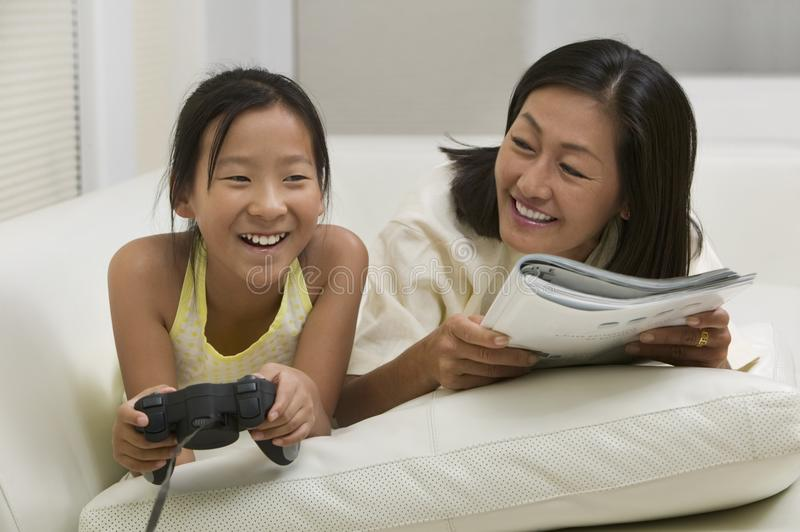 Mother reading with Daughter Playing Video game royalty free stock photography