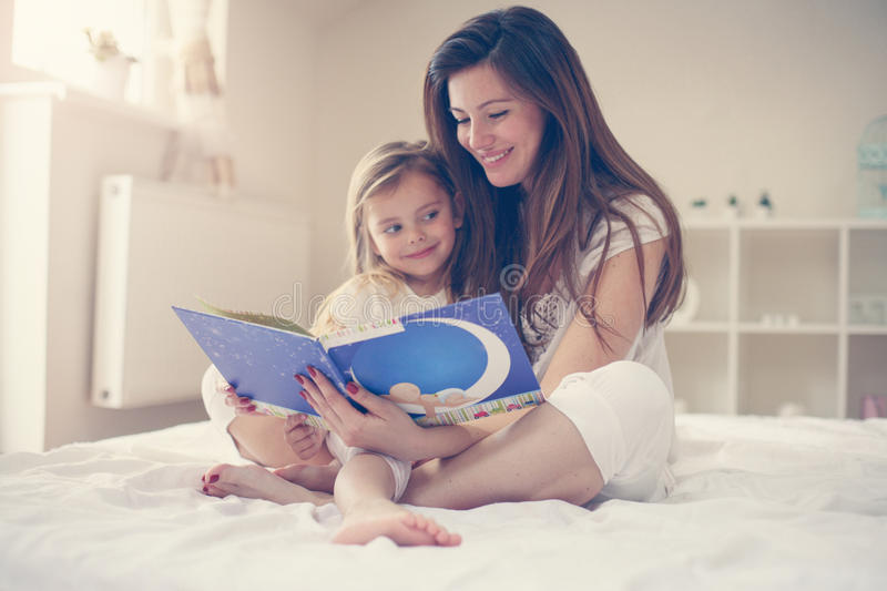 Mother reading her daughter the story after waking up. Mother wi. Mother with her daughter enjoying in the story stock photos
