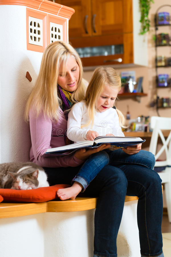 Mother reading night story to kid at home. Mother reading tired daughter good night story out of storytelling book stock images