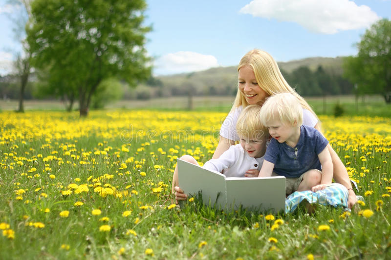 Mother Reading Story Book to Two Young Children Outside in Meadow. A happy young mother is sitting outside in a meadow of yallow Dandelion flowers, reading a