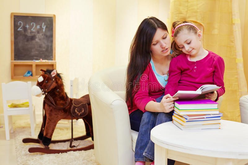 Mother reads book to daughter sitting in armchair