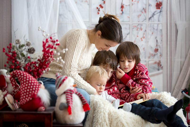 Mother reads book to her sons, children sitting in cozy armchair on a snowy winter day royalty free stock photo