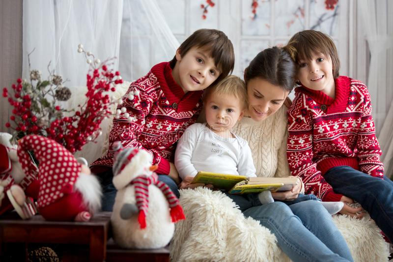 Mother reads book to her sons, children sitting in cozy armchair on a snowy winter day royalty free stock photography
