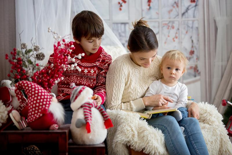 Mother reads book to her sons, children sitting in cozy armchair on a snowy winter day royalty free stock images