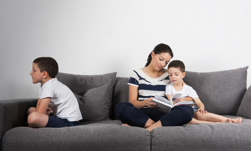 Mother reads an interesting book with her sons. Jealousy concept. Mother reads an interesting book with her son, and another son is offended on the opposite royalty free stock photography