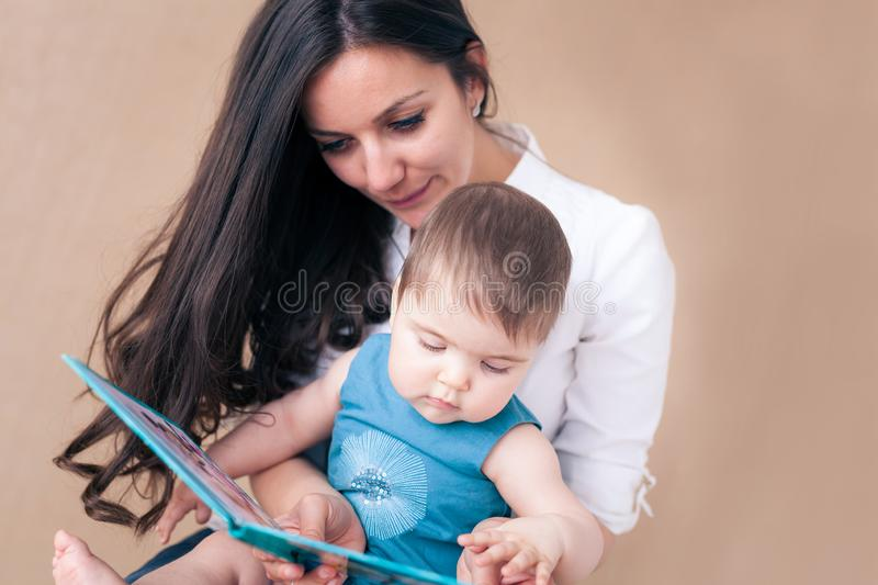 Mother reads a story to her baby girl stock images