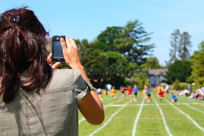Mother recording sports day royalty free stock images