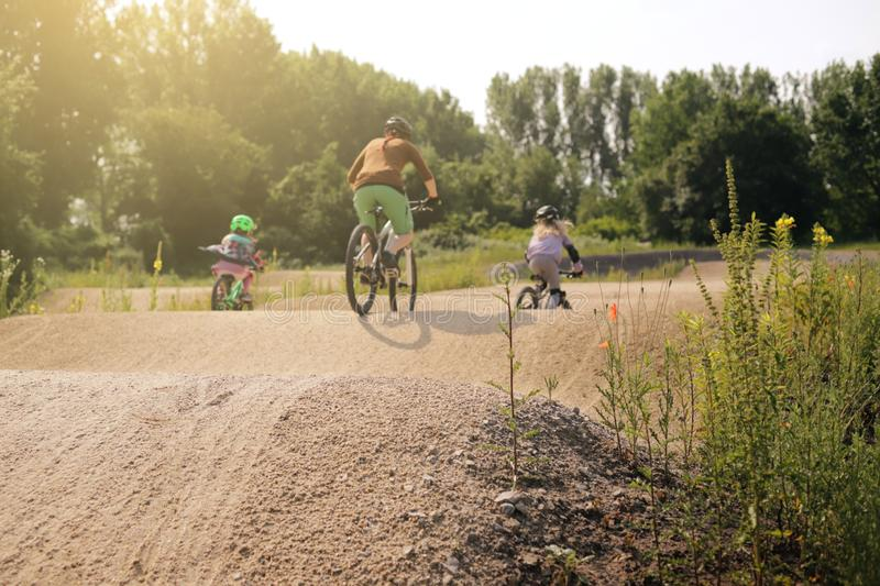 A mother rides bike together with her two daughters on a bicycle dirt track in bright summer light royalty free stock images