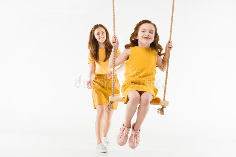 Mother riding little kid on swing stock photography