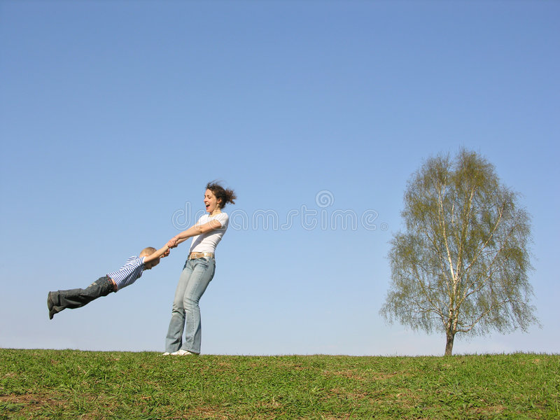 Mother rotate son on meadow. Spring royalty free stock photo