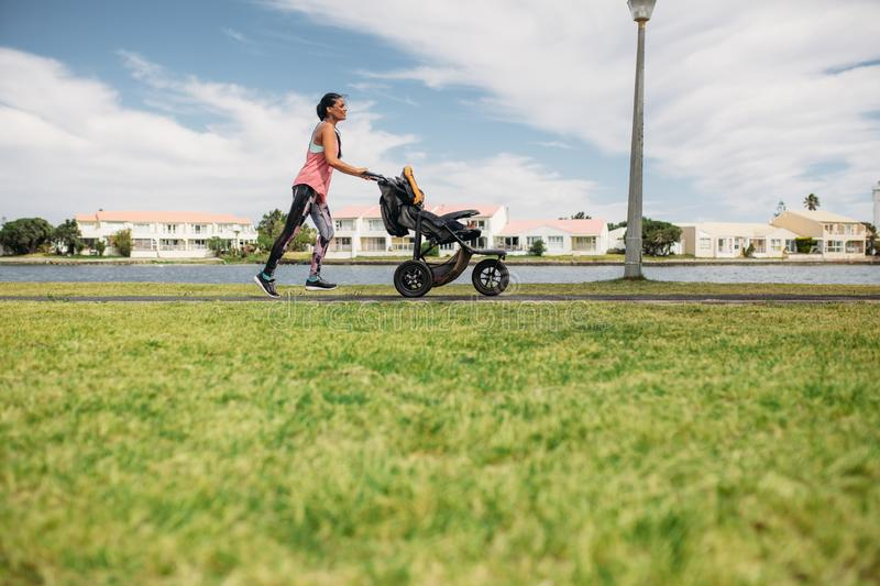 Mother running with a baby stroller in park royalty free stock image