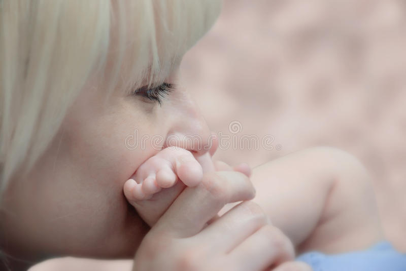 Mother's caress. Mother's gentle kiss baby leg royalty free stock images