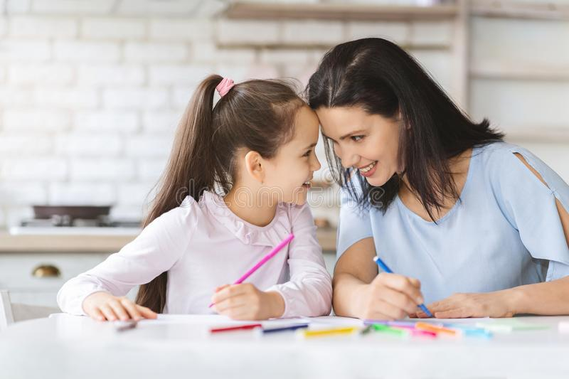 Cute little girl bonding with her mom, touching foreheads stock photos