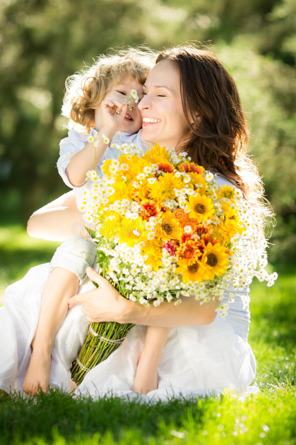 Mother`s day. Happy child and women with bouquet of spring flowers sitting on green grass. Mother`s day concept