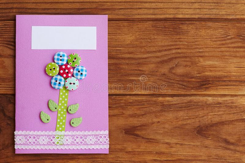 Mother`s day or birthday greeting card with flower on a wooden background with copy space for text. Simple handmade card royalty free stock photo