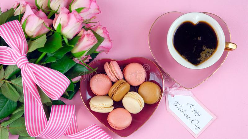 Mother`s Day coffee and macarons with roses gift overhead on pink wood table. royalty free stock images
