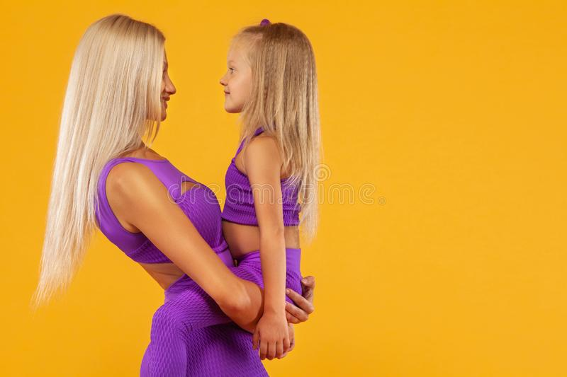 Mother`s day concept. Fitness family look. Young mother athlete and daughter exercise together indoors. stock photos