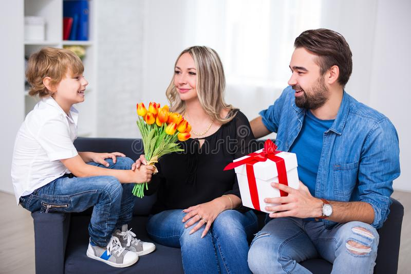 Mother`s day concept - little son and father giving flowers and. Gift to their wife and mother royalty free stock photo
