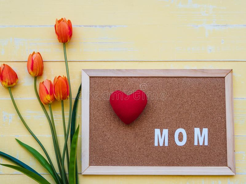 Mother`s day concept. red heart on the board with tulips flower stock images