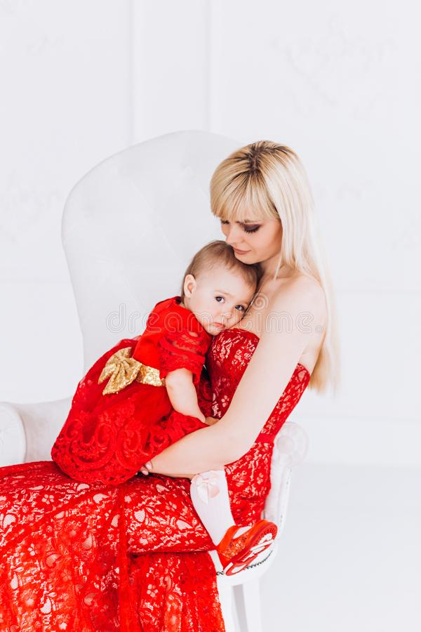 Mother`s Day and daughters. Advertising family values and traditions. Nice, family, good photo of mother and daughter in red dresses in the studio. Mother`s Day stock photos