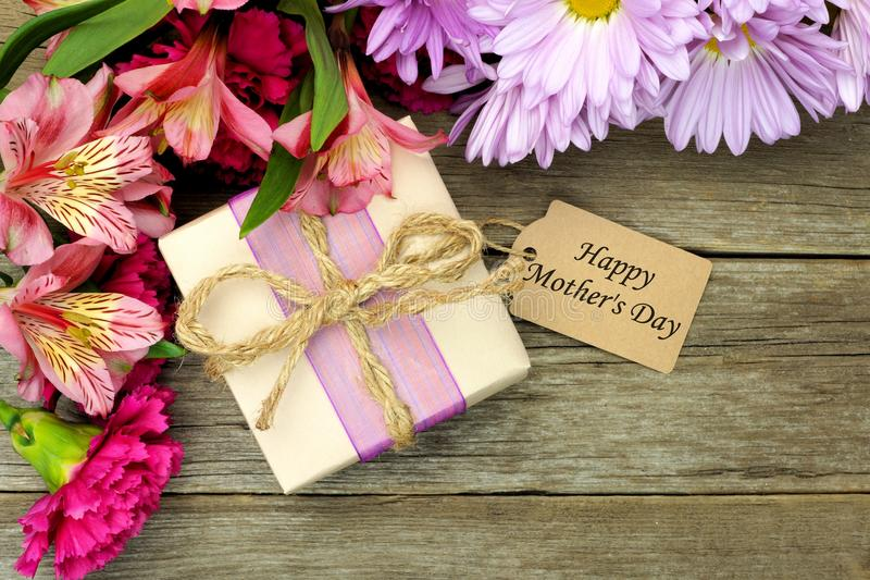 Mother's Day gift box and flowers on wood. Border of flowers with gift box and Happy Mother's Day tag against a rustic wood background stock photos
